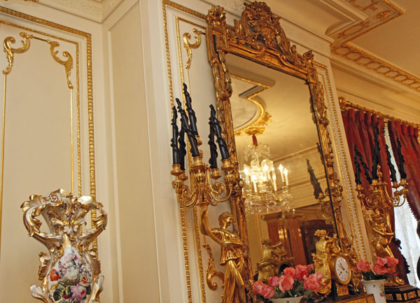 Gilded mirror over the fireplace mantle