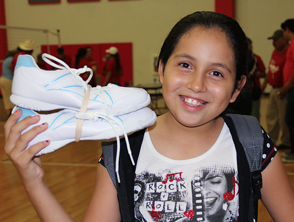 A child is thrilled to receive new shoes from Buckner Shoes for Orphan Souls®*